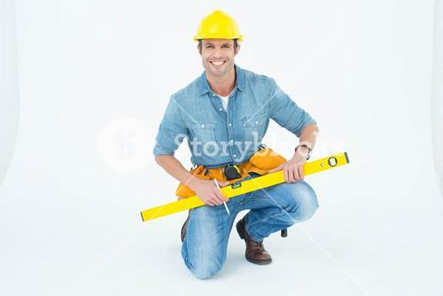 Worker using spirit level while kneeling over white background