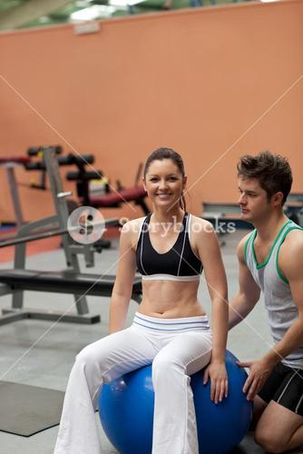 Bright young woman sitting on a musculation ball with her coach