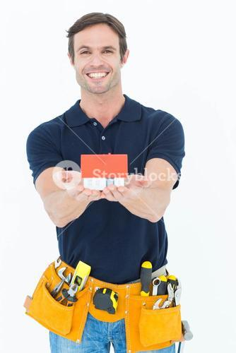 Male architect holding model home over white background
