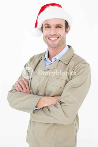 Delivery man in Santa hat standing arms crossed