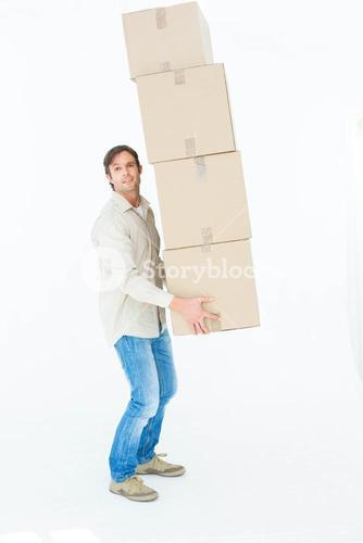 Portrait of courier man balancing cardboard boxes