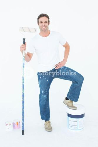 Man with paint bucket and roller on white background