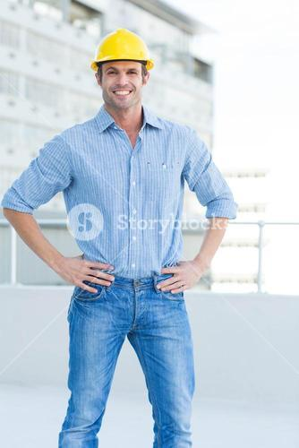 Happy male architect with hands on hips