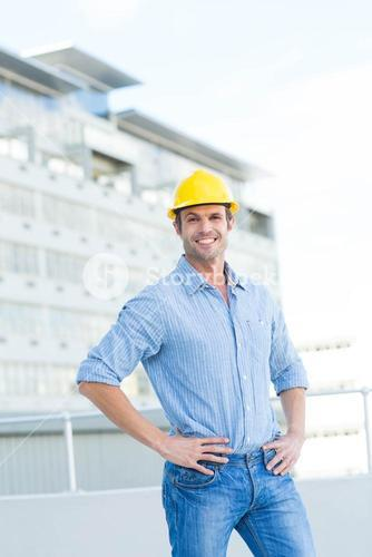 Handsome architect with hands on hips outdoors