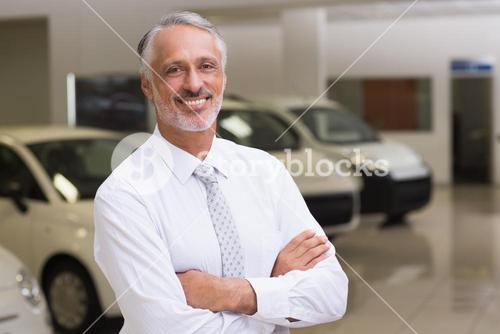 Smiling businessman standing with arms crossed