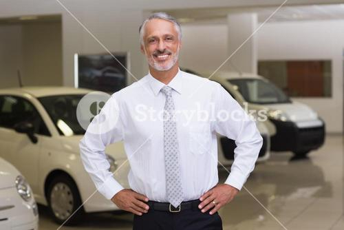 Smiling salesman standing with hands on hips