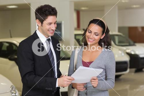 Salesperson showing clipboard to sign to customer