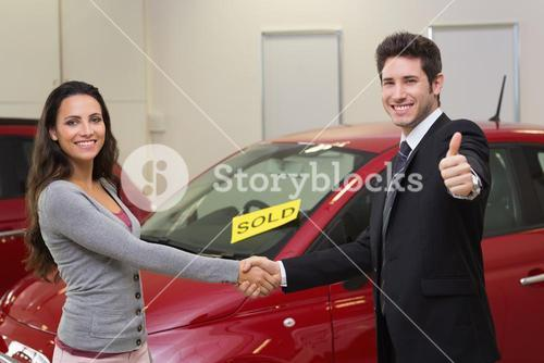 Person shaking hands in front of a sold car