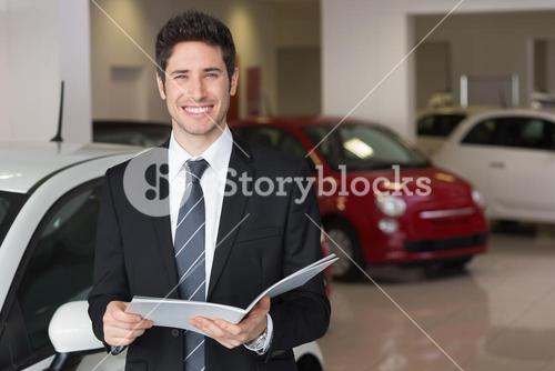 Businessman reading over a booklet smiling at camera
