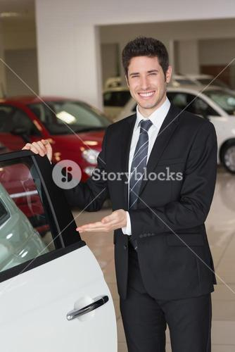 Smiling businessman showing a car for sale