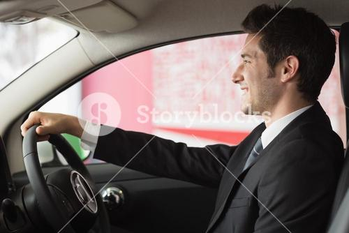Smiling businessman at the wheel sitting in a car for sale