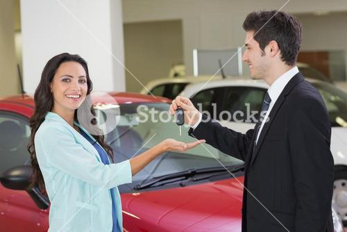 Smiling businessman giving car key to happy customer
