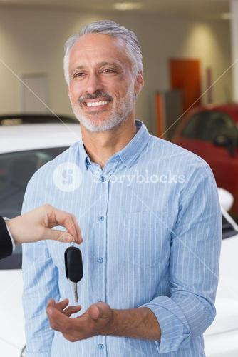 Businessman giving car key to happy customer
