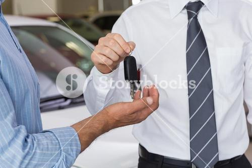 Businessman giving car key to customer