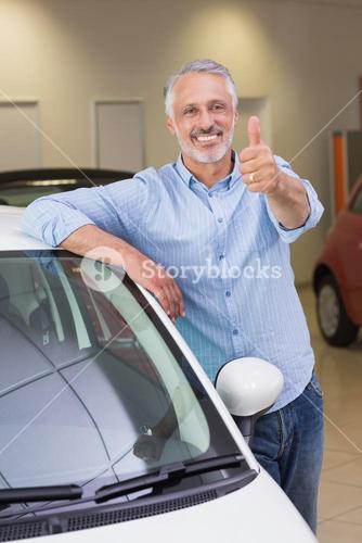 Smiling customer leaning on car while giving thumbs up
