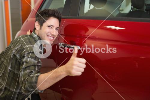 Smiling man hugging a red car while giving thumbs up