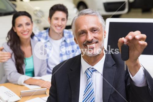 Smiling businessman showing a car key