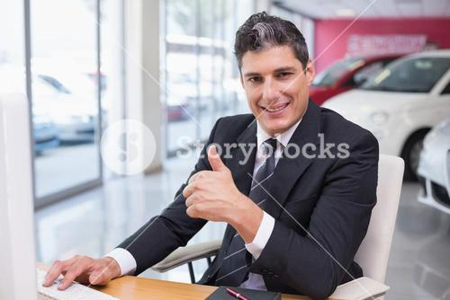 Smiling businessman giving thumbs up at his desk