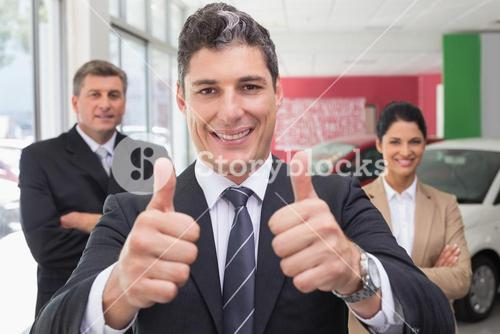 Smiling business team standing while one giving thumbs up