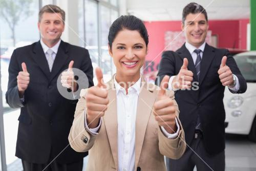 Smiling business team standing while giving thumbs up