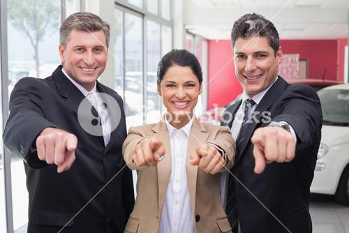 Smiling business team pointing at camera