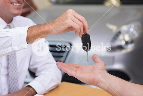 Salesman giving a customer car keys