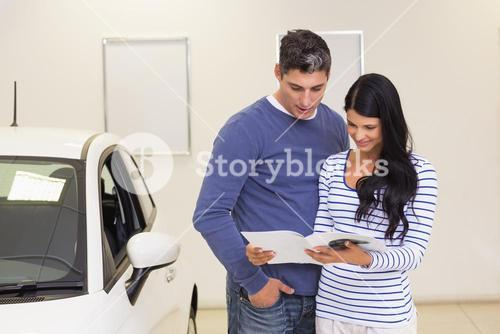 Smiling couple reading a booklet