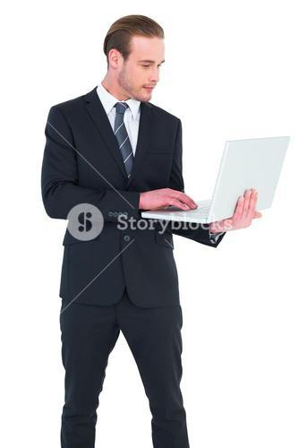 Businessman in suit typing on laptop