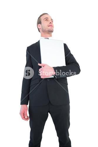 Businessman looking up holding laptop