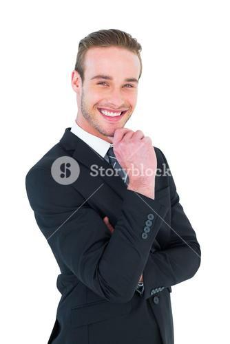 Happy businessman standing with hand on chin