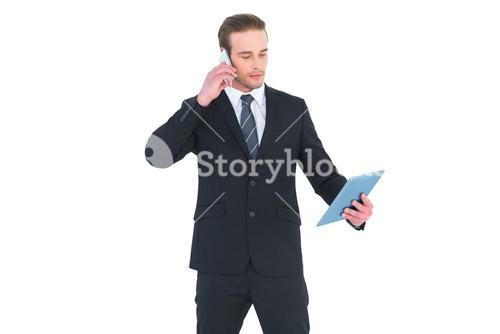 Serious businessman on the phone holding tablet