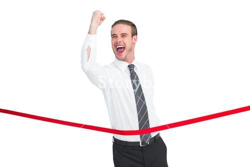 Businessman crossing the finish line while clenching fist