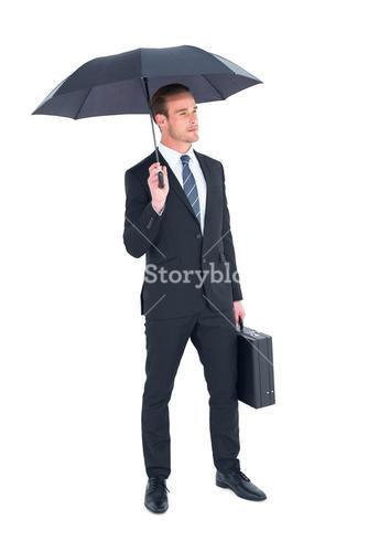 Businessman sheltering under umbrella holding briefcase