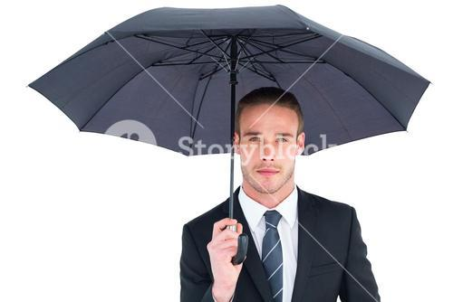 Unsmiling businessman sheltering under umbrella