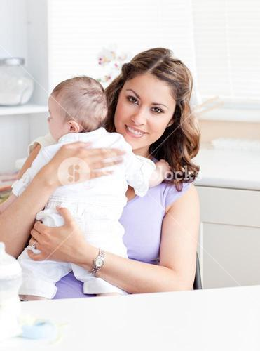 Positive young mother holding her baby in the kitchen