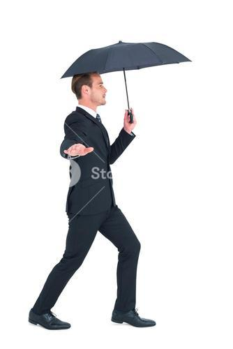 Concentrated businessman with umbrella walking