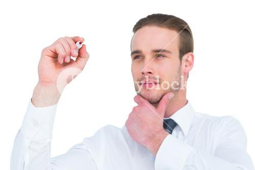 Focused businessman writing with hand on chin