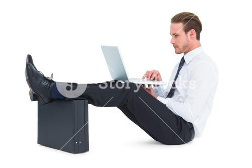 Businessman using laptop with feet up on briefcase