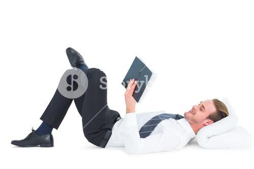 Relaxed businessman lying and reading book