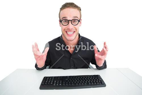Businessman in shirt making a face at desk