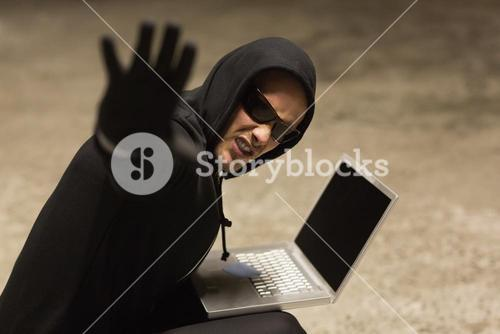 Frowning hacker in sunglasses gesturing