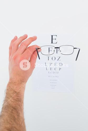 Hand holding glasses for a eye test