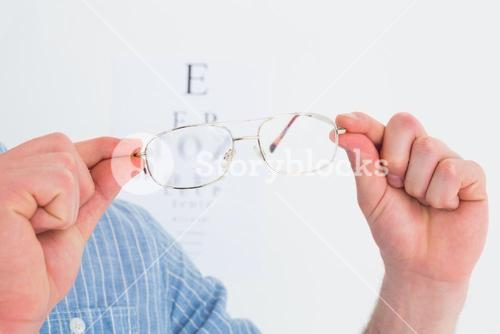 Hands holding glasses for eye test