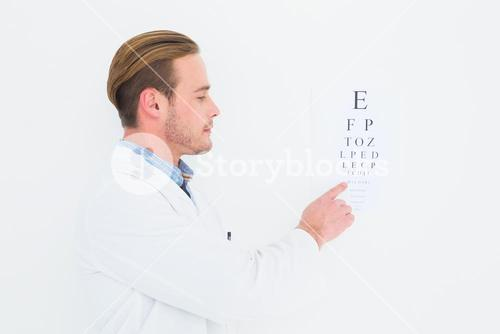 Optician in coat pointing eye test