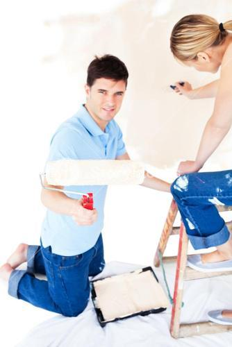 Happy couple painting a room