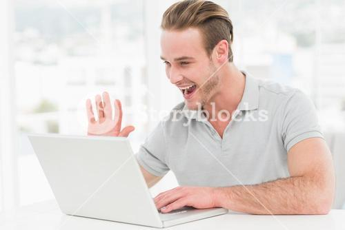 Happy businessman using laptop and gesturing