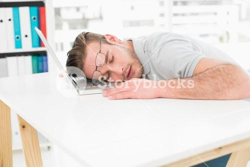 Tired businessman resting on laptop