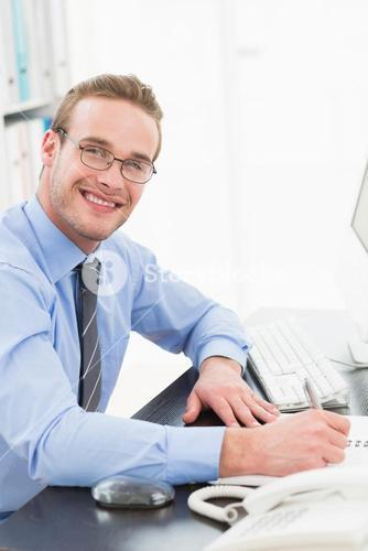Smiling businessman with glasses taking notes