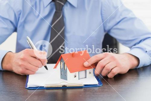 Businessman taking notes and holding miniature house