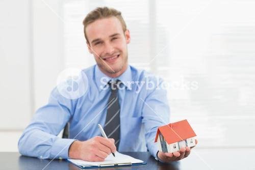 Businessman taking notes and showing miniature house